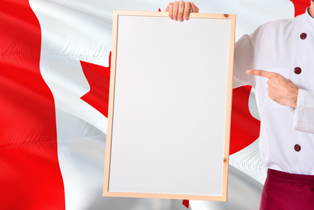 Canadian Chef holding blank whiteboard menu on Canada flag background. Cook wearing uniform pointing space for text.