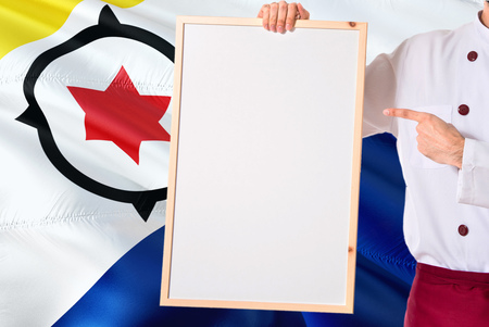 Chef holding blank whiteboard menu on Bonaire flag background. Cook wearing uniform pointing space for text.