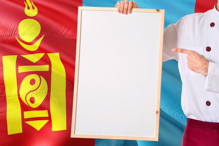 Mongolian Chef holding blank whiteboard menu on Mongolia flag background. Cook wearing uniform pointing space for text.