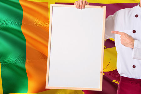 Sri Lankan Chef holding blank whiteboard menu on Sri Lanka flag background. Cook wearing uniform pointing space for text.