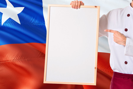 Chilean Chef holding blank whiteboard menu on Chile flag background. Cook wearing uniform pointing space for text. Stock Photo