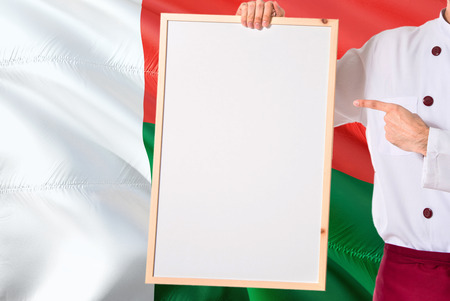 Malagasy Chef holding blank whiteboard menu on Madagascar flag background. Cook wearing uniform pointing space for text. Reklamní fotografie