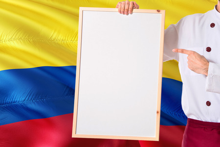 Colombian Chef holding blank whiteboard menu on Colombia flag background. Cook wearing uniform pointing space for text.