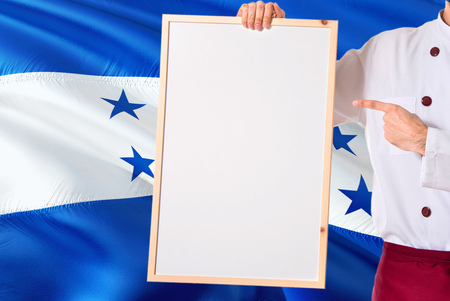Honduran Chef holding blank whiteboard menu on Honduras flag background. Cook wearing uniform pointing space for text.