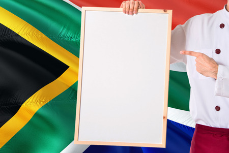 Chef holding blank whiteboard menu on South Africa flag background. Cook wearing uniform pointing space for text.