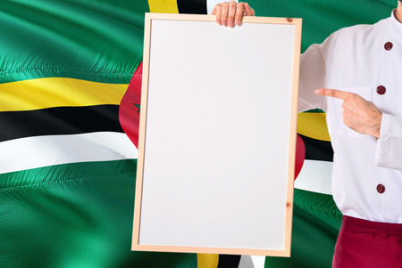 Dominican Chef holding blank whiteboard menu on Dominica flag background. Cook wearing uniform pointing space for text. Stock Photo