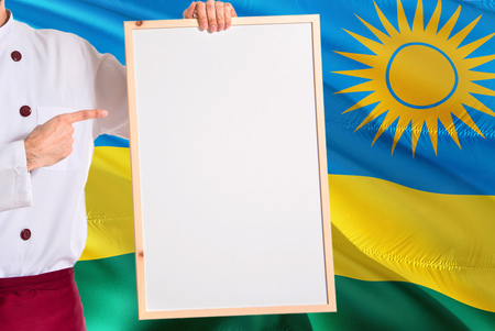 Rwandan Chef holding blank whiteboard menu on Rwanda flag background. Cook wearing uniform pointing space for text.
