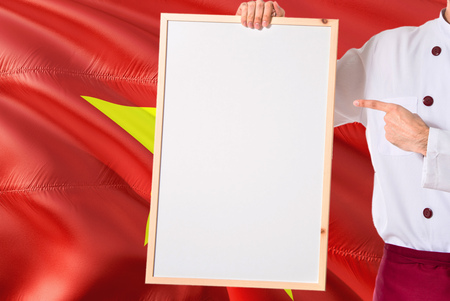 Vietnamese Chef holding blank whiteboard menu on Vietnam flag background. Cook wearing uniform pointing space for text.