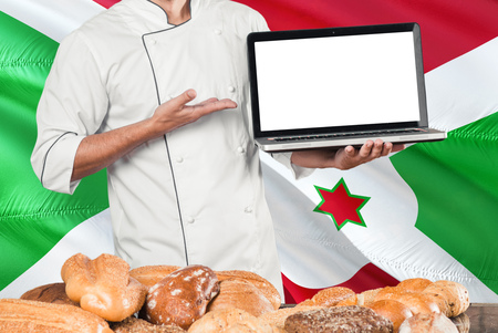 Burundian Baker holding laptop on Burundi flag and breads background. Chef wearing uniform pointing blank screen for copy space. Stock Photo