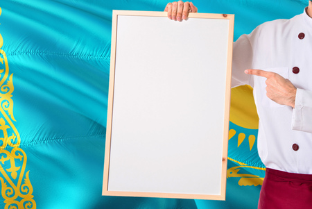 Kazakh Chef holding blank whiteboard menu on Kazakhstan flag background. Cook wearing uniform pointing space for text. 免版税图像