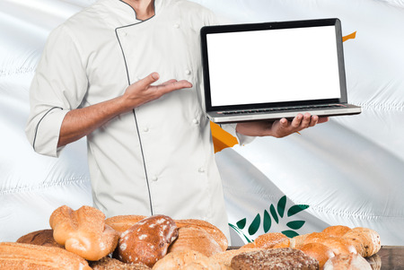 Cypriot Baker holding laptop on Cyprus flag and breads background. Chef wearing uniform pointing blank screen for copy space. Stock Photo