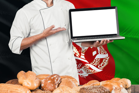 Afghan Baker holding laptop on Afghanistan flag and breads background. Chef wearing uniform pointing blank screen for copy space.