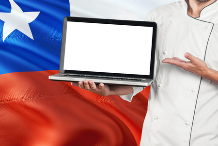 Chilean Chef holding laptop with blank screen on Chile flag background. Cook wearing uniform and pointing laptop for copy space. Banque d'images