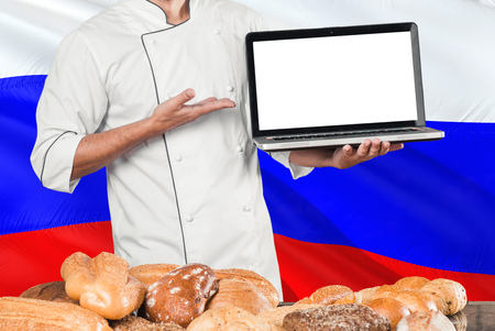 Russian Baker holding laptop on Russia flag and breads background. Chef wearing uniform pointing blank screen for copy space. Stock Photo