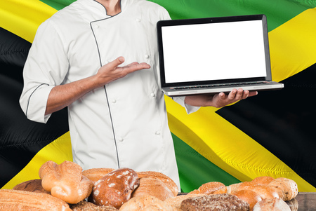 Jamaican Baker holding laptop on Jamaica flag and breads background. Chef wearing uniform pointing blank screen for copy space.