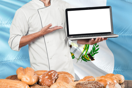 Guatemalan Baker holding laptop on Guatemala flag and breads background. Chef wearing uniform pointing blank screen for copy space.