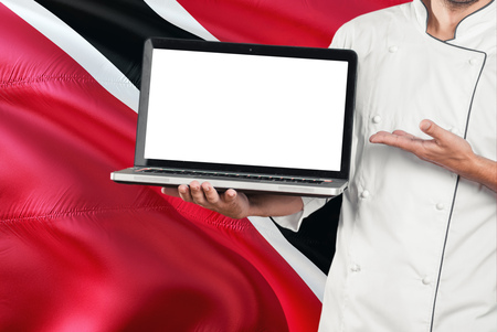 Chef holding laptop with blank screen on Trinidad And Tobago flag background. Cook wearing uniform and pointing laptop for copy space. Stock Photo