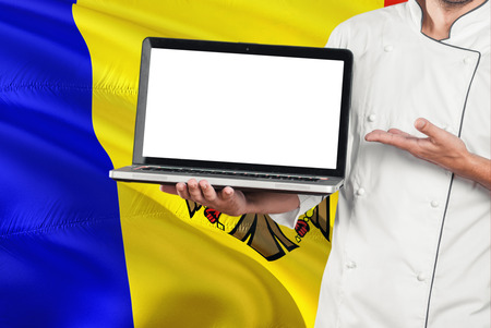 Moldovan Chef holding laptop with blank screen on Moldova flag background. Cook wearing uniform and pointing laptop for copy space. Foto de archivo