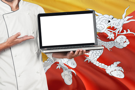 Bhutanese Chef holding laptop with blank screen on Bhutan flag background. Cook wearing uniform and pointing laptop for copy space.