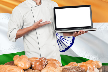 Indian Baker holding laptop on India flag and breads background. Chef wearing uniform pointing blank screen for copy space.