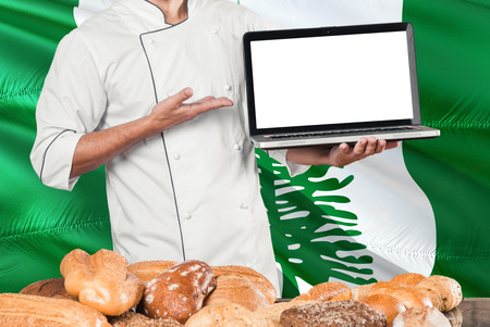 Baker holding laptop on Norfolk Island flag and breads background. Chef wearing uniform pointing blank screen for copy space. 스톡 콘텐츠