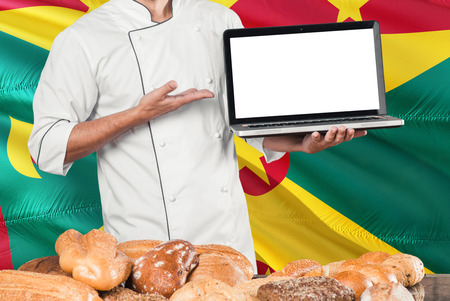 Grenadian Baker holding laptop on Grenada flag and breads background. Chef wearing uniform pointing blank screen for copy space. Stock Photo