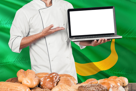 Mauritanian Baker holding laptop on Mauritania flag and breads background. Chef wearing uniform pointing blank screen for copy space.