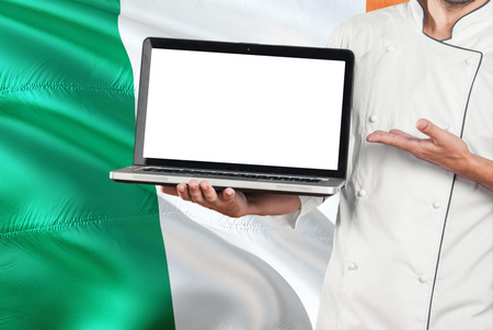 Irish Chef holding laptop with blank screen on Ireland flag background. Cook wearing uniform and pointing laptop for copy space.
