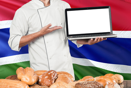 Gambian Baker holding laptop on Gambia flag and breads background. Chef wearing uniform pointing blank screen for copy space.