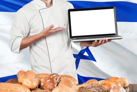 Israeli Baker holding laptop on Israel flag and breads background. Chef wearing uniform pointing blank screen for copy space. Stock Photo