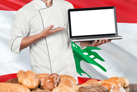 Lebanese Baker holding laptop on Lebanon flag and breads background. Chef wearing uniform pointing blank screen for copy space.