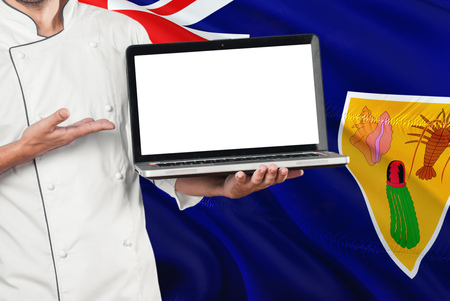 Chef holding laptop with blank screen on Turks And Caicos Islands flag background. Cook wearing uniform and pointing laptop for copy space.