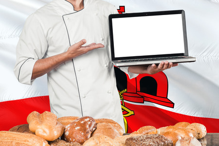 Baker holding laptop on Gibraltar flag and breads background. Chef wearing uniform pointing blank screen for copy space.