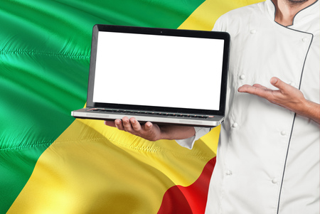 Congolese Chef holding laptop with blank screen on Republic Of The Congo flag background. Cook wearing uniform and pointing laptop for copy space. Standard-Bild