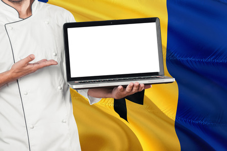 Barbadian Chef holding laptop with blank screen on Barbados flag background. Cook wearing uniform and pointing laptop for copy space.