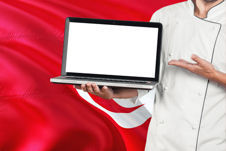 Tunisian Chef holding laptop with blank screen on Tunisia flag background. Cook wearing uniform and pointing laptop for copy space.