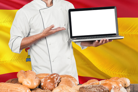 Spanish Baker holding laptop on Spain flag and breads background. Chef wearing uniform pointing blank screen for copy space. Stock Photo