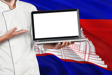 Cambodian Chef holding laptop with blank screen on Cambodia flag background. Cook wearing uniform and pointing laptop for copy space.