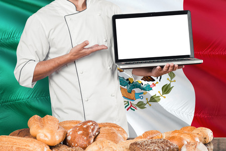 Mexican Baker holding laptop on Mexico flag and breads background. Chef wearing uniform pointing blank screen for copy space.