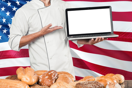 American Baker holding laptop on United States flag and breads background. Chef wearing uniform pointing blank screen for copy space.