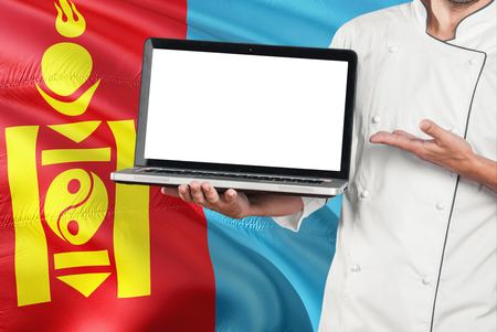 Mongolian Chef holding laptop with blank screen on Mongolia flag background. Cook wearing uniform and pointing laptop for copy space.