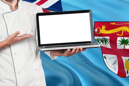 Fijian Chef holding laptop with blank screen on Fiji flag background. Cook wearing uniform and pointing laptop for copy space.