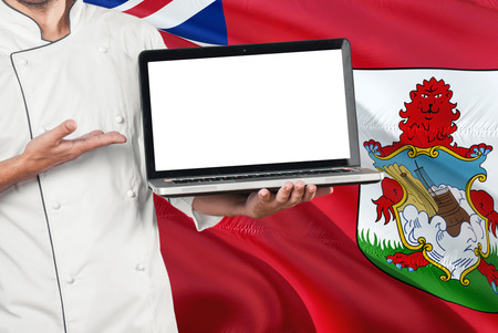 Chef holding laptop with blank screen on Bermuda flag background. Cook wearing uniform and pointing laptop for copy space.