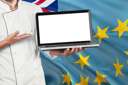Tuvaluan Chef holding laptop with blank screen on Tuvalu flag background. Cook wearing uniform and pointing laptop for copy space. Banco de Imagens