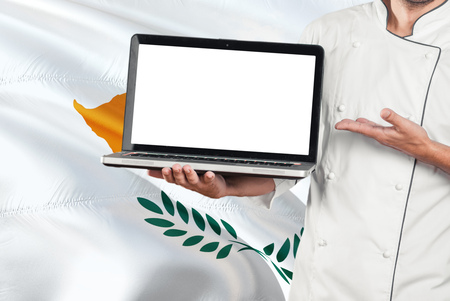 Cypriot Chef holding laptop with blank screen on Cyprus flag background. Cook wearing uniform and pointing laptop for copy space. 版權商用圖片