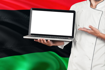 Libyan Chef holding laptop with blank screen on Libya flag background. Cook wearing uniform and pointing laptop for copy space. Archivio Fotografico