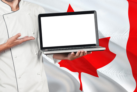 Canadian Chef holding laptop with blank screen on Canada flag background. Cook wearing uniform and pointing laptop for copy space.