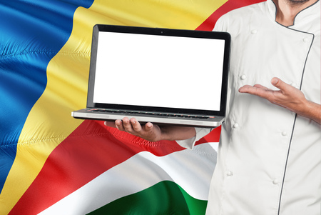 Seychellois Chef holding laptop with blank screen on Seychelles flag background. Cook wearing uniform and pointing laptop for copy space.