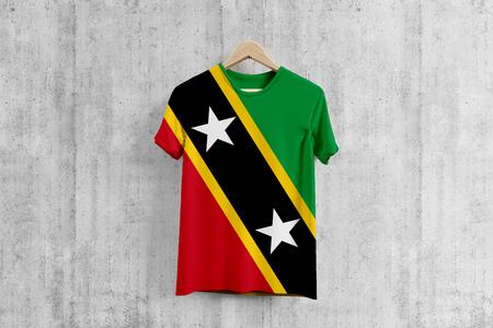 Saint Kitts And Nevis flag T-shirt on hanger, team uniform design idea for garment production. National wear. Stock fotó