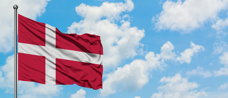 Denmark flag waving in the wind against white cloudy blue sky. Diplomacy concept, international relations.